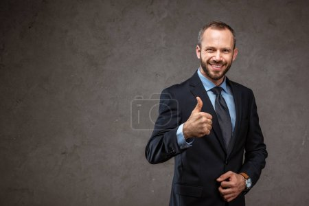 Foto de Happy bearded businessman in suit showing thumb up on grey - Imagen libre de derechos