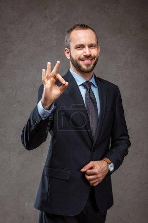 Photo pour Heureux homme d'affaires barbu en costume montrant ok signe sur gris - image libre de droit