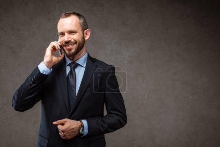 Photo pour Homme d'affaires joyeux parlant sur smartphone et souriant sur gris - image libre de droit