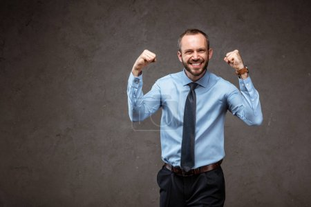 Photo for Happy businessman in suit gesturing while celebrating on grey - Royalty Free Image