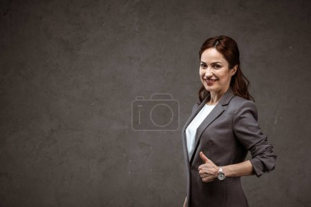 Photo for Cheerful brunette businesswoman showing thumb up and smiling on grey - Royalty Free Image