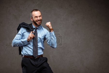 Photo for Cheerful businessman in suit gesturing while celebrating on grey - Royalty Free Image