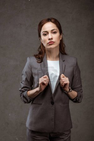 Photo for Attractive brunette businesswoman in formal wear looking at camera on grey - Royalty Free Image