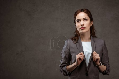 Photo for Thoughtful brunette businesswoman in formal wear standing on grey - Royalty Free Image