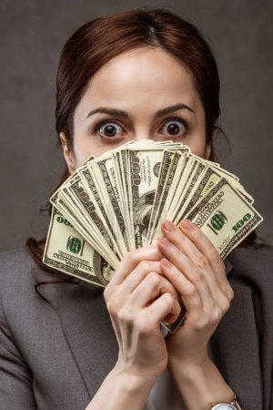 Photo for Shocked brunette woman covering face with dollar banknotes on grey - Royalty Free Image