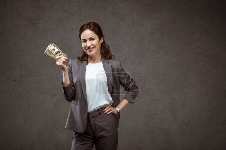 Photo for Happy businesswoman standing with hand on hip and holding dollar banknotes on grey - Royalty Free Image