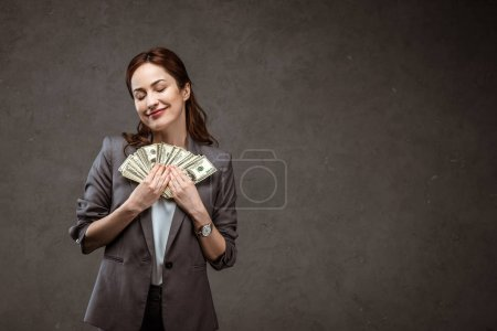 Photo for Happy businesswoman standing with closed eyes and holding dollar banknotes on grey - Royalty Free Image