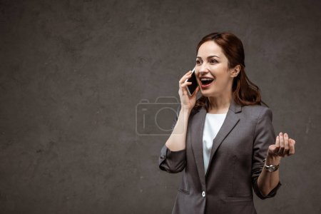 Photo for Happy brunette businesswoman talking on smartphone and gesturing on grey - Royalty Free Image