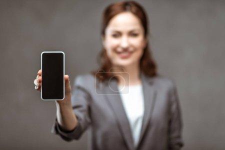 Photo pour Foyer sélectif de femme d'affaires gaie tenant smartphone avec écran blanc sur gris - image libre de droit