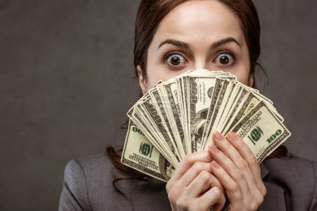 Photo for Surprised brunette businesswoman covering face with dollar banknotes on grey - Royalty Free Image