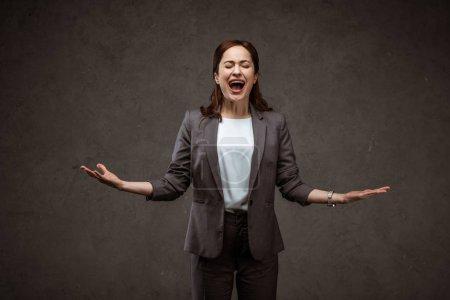 Photo pour Femme de brunette restant avec les mains tendues et criant sur le gris - image libre de droit