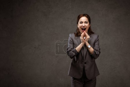 Photo for Excited brunette woman in formal wear standing and screaming on grey - Royalty Free Image