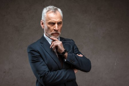 Photo for Thoughtful businessman in suit standing and thinking on grey - Royalty Free Image