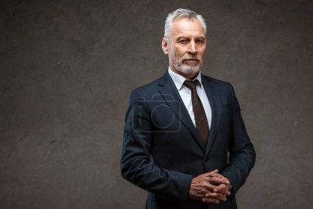 Photo pour Homme d'affaires réussi dans la position de costume avec les mains serrées sur le gris - image libre de droit
