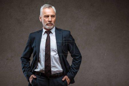 Photo pour Homme d'affaires barbu réussi restant avec des mains dans des poches sur le gris - image libre de droit