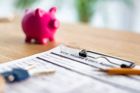 selective focus of clipboard with new house loan lettering on document near pencil, keys and pink piggy bank