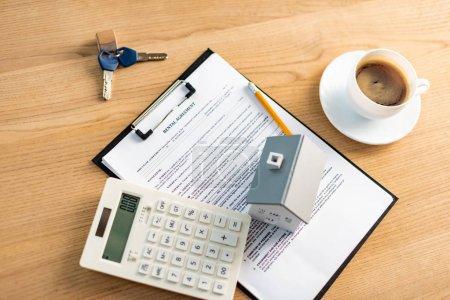 Photo pour Vue du haut de la tasse de café près du presse-papiers avec lettrage de contrat de location sur la table - image libre de droit