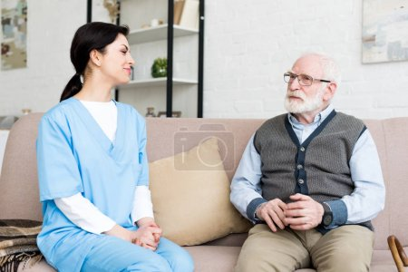 Happy nurse sitting on couch, looking at grey haired man