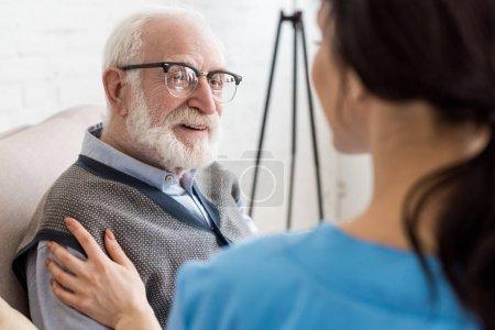 Photo pour Focus sélectif de l'homme gai et aux cheveux gris regardant l'infirmière - image libre de droit