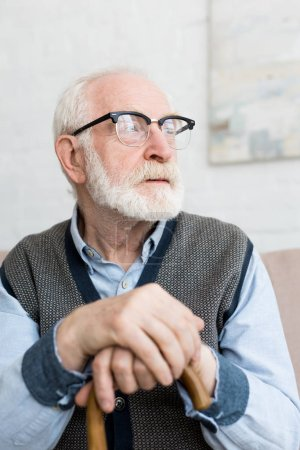 Photo for Calm and sad senior man with walking stick looking away, sitting in bright room - Royalty Free Image