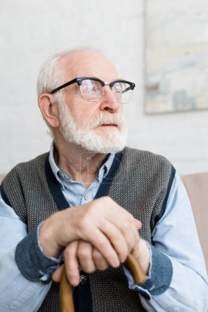 Photo pour Homme aîné calme et triste avec le bâton de marche regardant loin, s'asseyant dans la chambre lumineuse - image libre de droit