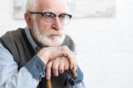Photo pour Homme aîné triste et barbu avec le bâton de marche s'asseyant dans la chambre, regardant loin - image libre de droit
