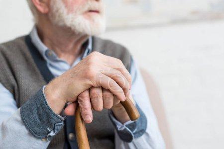 Photo pour Vue recadrée de l'homme âgé avec le bâton de marche dans les mains - image libre de droit