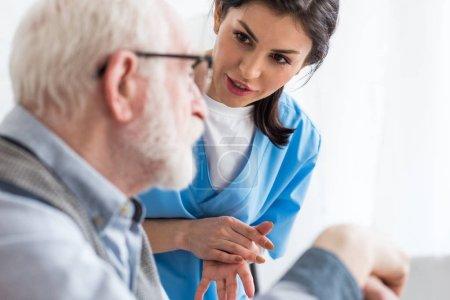 Photo pour Concentration sélective d'une infirmière calme parlant à un patient âgé - image libre de droit