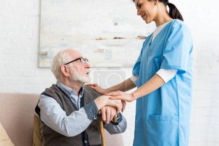 Photo pour Vue latérale de l'homme âgé et l'infirmière restant dans la chambre, regardant l'un l'autre - image libre de droit