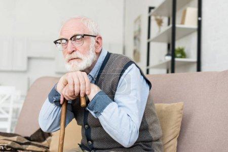 Photo pour Homme aux cheveux barbu et gris s'asseyant dans la pièce lumineuse, mettant la main sur le bâton de marche - image libre de droit