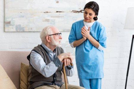 Nurse talking to bearded senior man, standing inside bright room