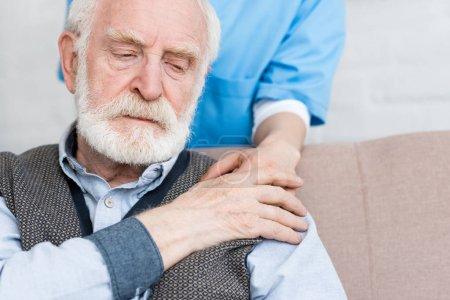 Photo pour Infirmière mettant la main sur l'homme triste aîné - image libre de droit