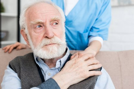 Photo for Nurse putting hand on sad and grey haired patient - Royalty Free Image