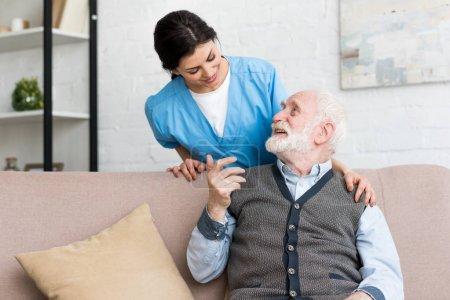 Arzt steht hinter älterem Mann und spricht mit glücklichem Patienten