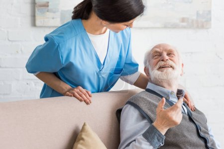 Happy senior man looking at nurse, sitting on couch
