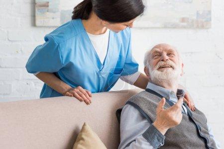 Heureux homme âgé regardant infirmière, assis sur le canapé