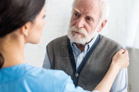 Photo pour Focus sélectif de l'infirmière mettant la main sur l'homme sérieux et gris aux cheveux - image libre de droit