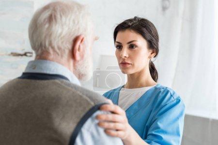 Photo pour Focus sélectif de l'infirmière sérieuse mettant la main sur l'homme aux cheveux gris - image libre de droit
