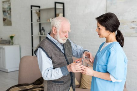 Photo pour Vue latérale de l'infirmière donnant des pilules avec de l'eau à l'homme aux cheveux gris - image libre de droit