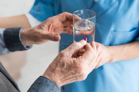 Photo pour Vue recadrée des pilules de fixation d'homme âgé dans la main, tandis que le docteur donnant le verre avec l'eau au patient - image libre de droit