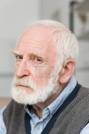 Photo for Sad and bearded grey haired man looking at camera - Royalty Free Image