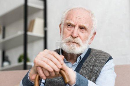 Photo pour Homme aux cheveux gris pensive et solitaire avec bâton de marche regardant loin - image libre de droit