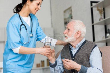Photo pour Infirmière donnant un verre d'eau à un homme âgé avec une pilule à la main - image libre de droit