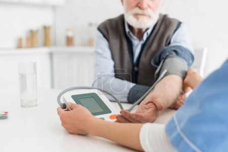 Photo for Cropped view of senior man and nurse measuring blood pressure - Royalty Free Image