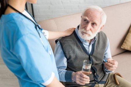 Photo pour Infirmière mettant la main sur l'homme aux cheveux gris avec la pilule et le verre de l'eau - image libre de droit