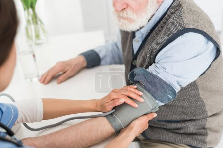 Cropped view of nurse putting hands on grey haired man, measuring blood pressure