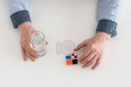 Photo for Cropped view of senior man holding glass with water and pills in hands - Royalty Free Image
