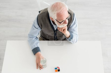 Photo pour Vue aérienne de l'homme pensive regardant loin, assis derrière la table avec des pilules et l'eau dans le verre - image libre de droit
