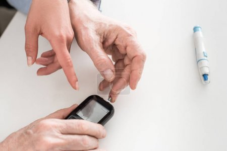 Photo for Cropped view of man hands measuring blood sugar, while woman pointing with finger on display - Royalty Free Image