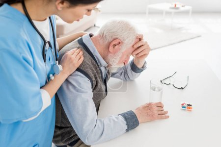 Photo for High angle view of nurse putting hands on sad and grey haired man - Royalty Free Image
